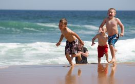 Kids running on beach in Lakes Entrance