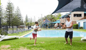 Dad and son playing with ball by the pool