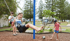 three young boys playing on the swing set at port macquaire