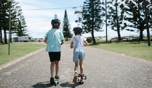 Two kids on scooters in the park