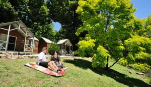 Couple sitting outside cabin inside a Bright holiday park