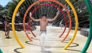 Kid running through colourful water fountain inside a Bright holiday and caravan park