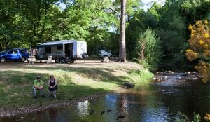 Couple sitting by the river inside a bright caravan park