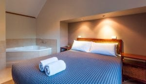 cabin accommodation bedroom with a spa inside a bright holiday park