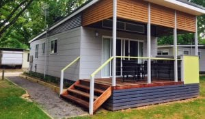 Exterior of cabin accommodation with a deck inside a Bright holiday park