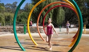 Young girl running through colourful fountain inside a Bright holiday park