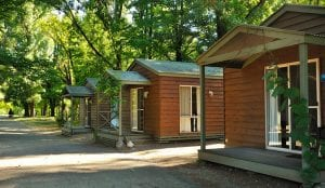 Row of cabins surrounded by trees inside a Bright holiday park