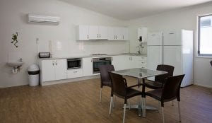 interior of camp kitchen including seating areas, large kitchen and air-conditioning