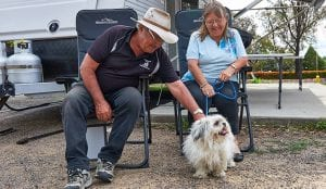 couple and their small dog sitting outside their caravan in Bathurst