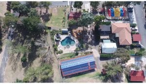 ariel view of a bathurst holiday park showing cabin roofs, trees and a swimming pool