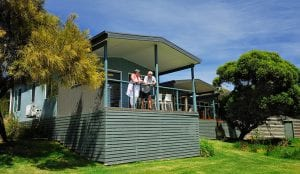 Two travelers standing on balcony of Port Campbell accommodation