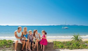 Family of five sitting in front of a beach near Yeppoon