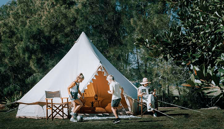 family sitting and playing with a ball outside of a bell tent at NRMA Ocean Beach Holiday Resort