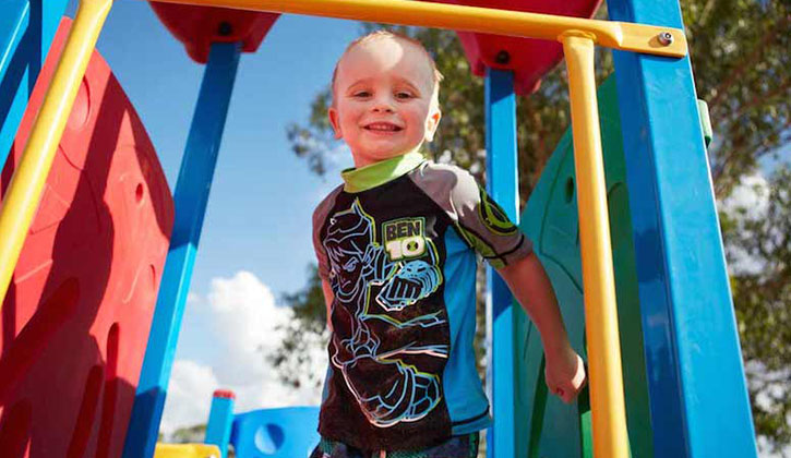 Young boy smiling while standing on a playground inside a Yarrawonga caravan park