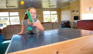 Young girl playing ping pong in the recreation room