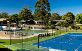 Tennis court with pool in background at a Halls Gap caravan park